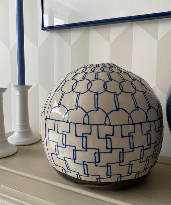 Geometric pottery pot in blue and cream on a beige bookshelf with white candlesticks behind.