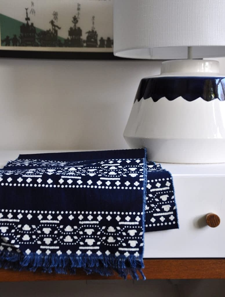 An Asian motif handmade indigo scarf on a dressing table with a ceramic table lamp.