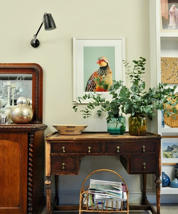 A giclée digital art print of a partridge above a mahogany desk and vase with eucalyptus.
