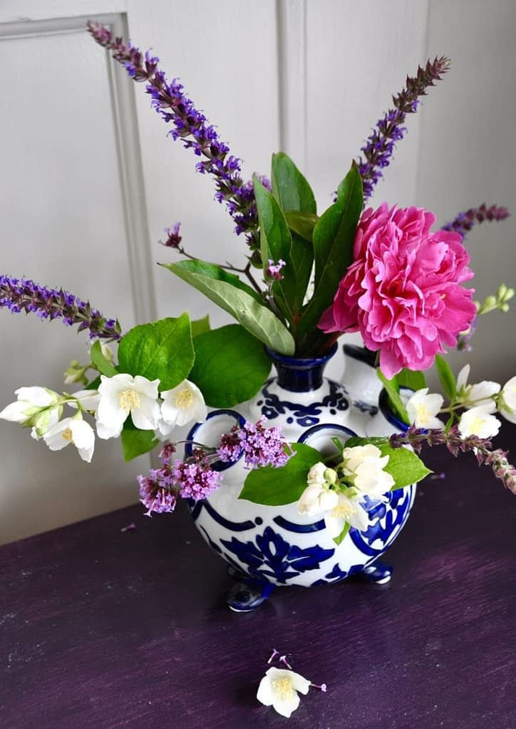 Dutch-style, Delft-blue and white, small vase filled with pink and purple summer blooms and displayed on a purple painted wooden surface.