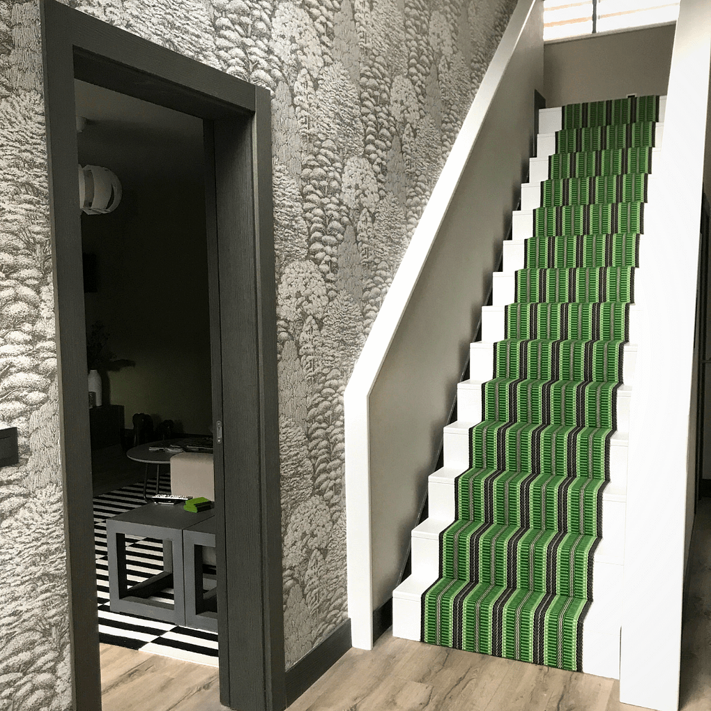 A vibrant, green, woven, striped, stair runner in a modern grey-toned hallway.