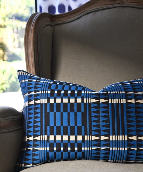 A blue geometric cushion with an African, tribal-pattern-inspired design on a French armchair.