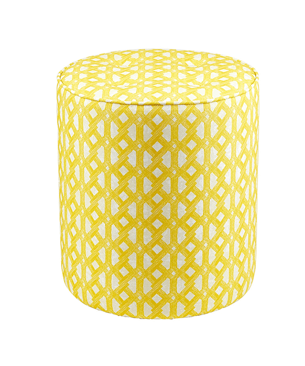 A yellow pouffe or upholstered stool with stylish, modern African tribal pattern upholstery.