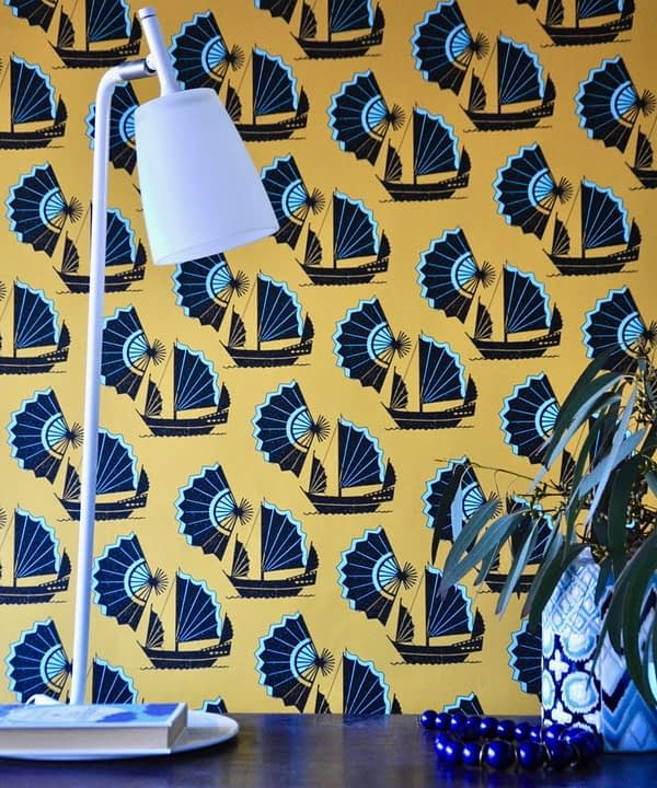 A bold yellow and turquoise wallpaper depicting Chinese junk ships and fans.