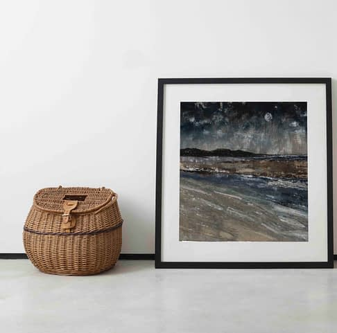 Irish wall art print Five Finger Strand is leaned against a wall next to an old-fashioned wicker picnic basket.