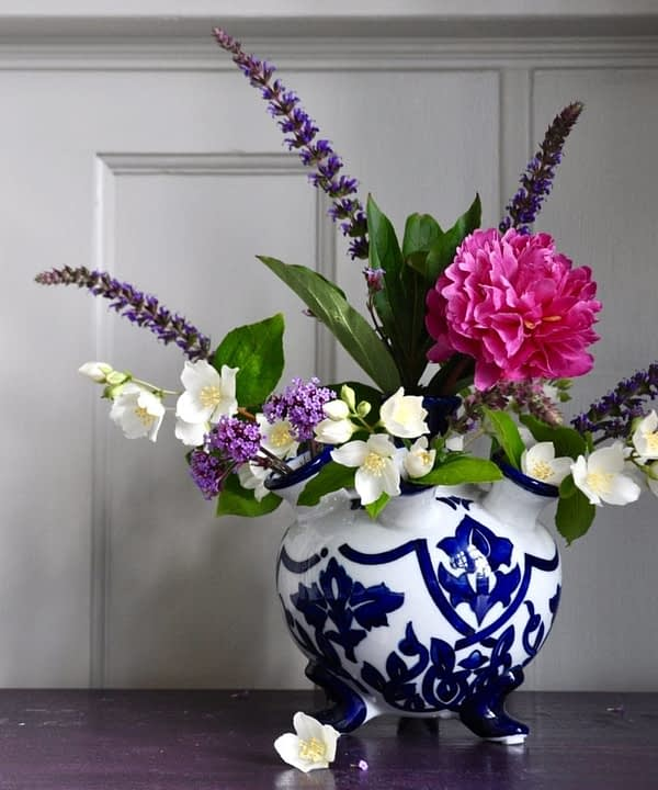 Dutch blue and white small tulip vase with pink, cream and purple summer blooms on a purple sideboard.