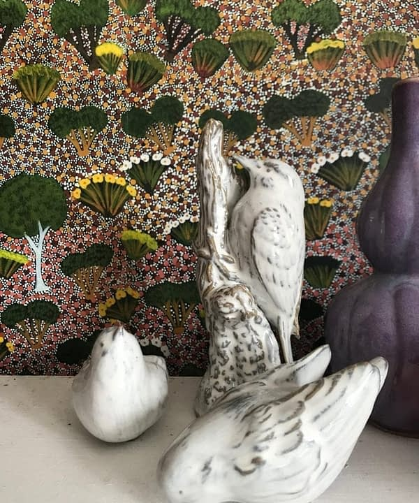 A collection of white glazed ceramic birds with a botanical Aboriginal art wallpaper backdrop.