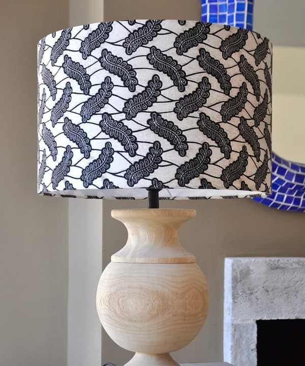 A stylish monochrome drum lampshade available in two sizes teamed with a simple, urn-shaped wooden base.