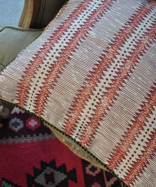 Red and white cushion with handprinted zigzag stripes on linen fabric.