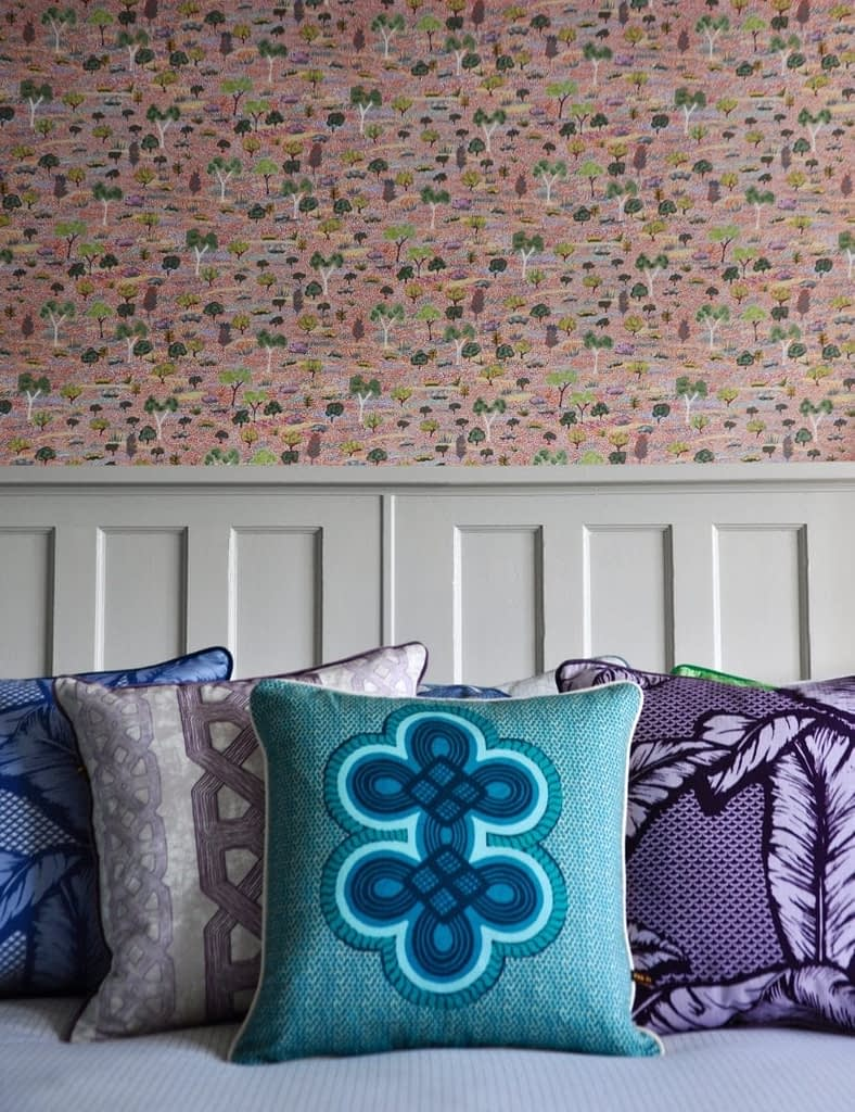 Colourful Ghanaian and Nigerian style cushions grouped on a bed against Aboriginal wallpaper in the background.