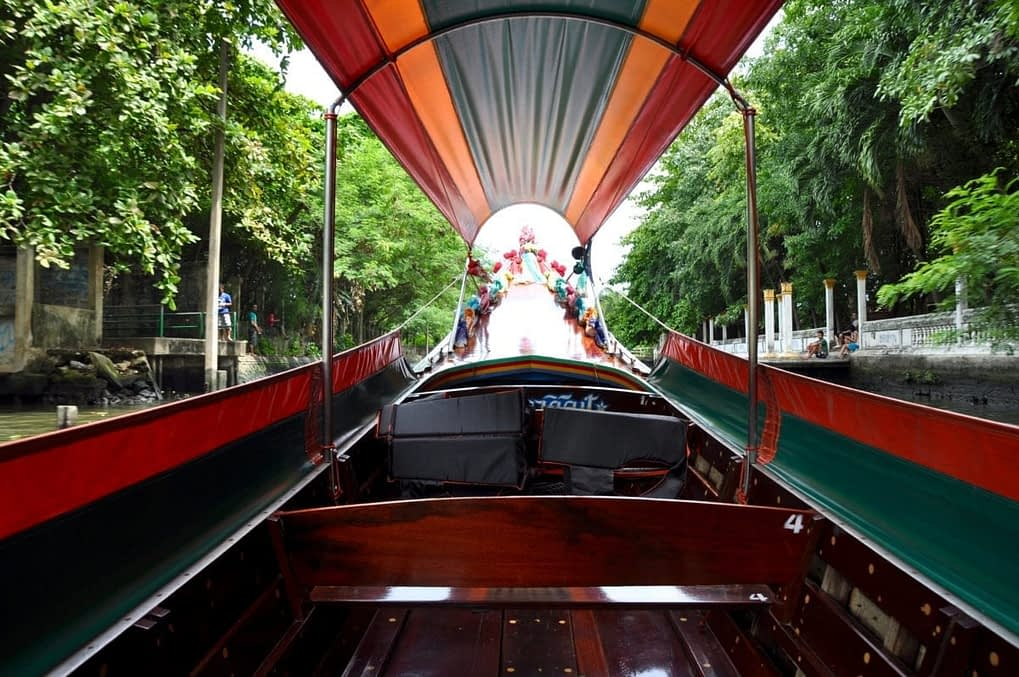 View from inside a Thai longtail boat travelling along the Chao Phraya river in Bangkok.