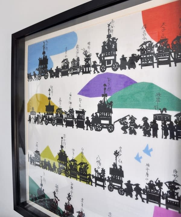 A colourful, Japanese silkscreen print depicting the Gion festival in a simple, black frame.