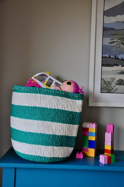 A stripy jade woven basket with colourful kids toys and lego inside on a teal sideboard.