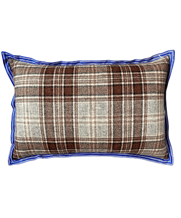 The brown woollen check reverse of a floral linen cushion with blue striped trim.
