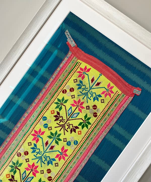 Framed embroidery art showcasing a vintage, embroidered Thai panel in yellow on a turquoise silk mount.