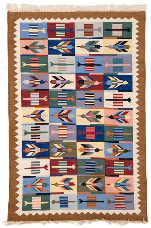 A multi-coloured, flèche-motif, Aztec style rug from Telescope Style.