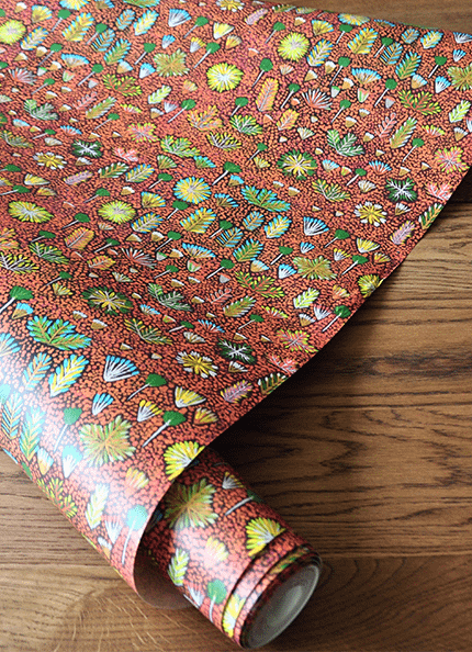 A roll of the 'Daisy' Aboriginal art wallpaper in brown.
