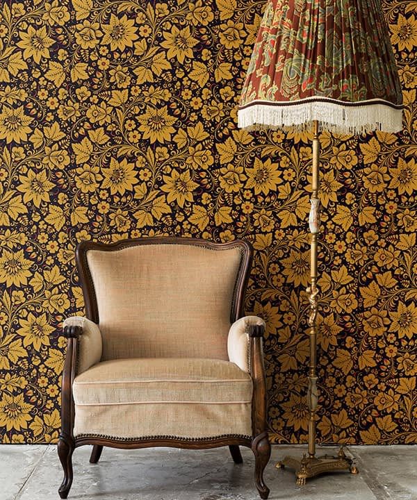 A vintage chair and lampshade with Russian folk art wallpaper in gold as the backdrop.