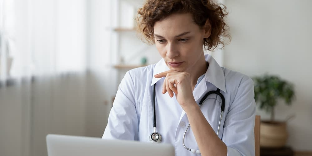 Concentrated young female physician working on computer doing online research